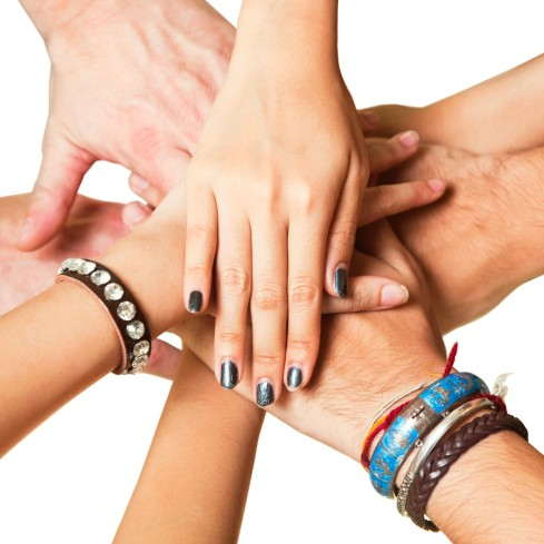 Close-up of human hands clasped together in unity against white backdrop